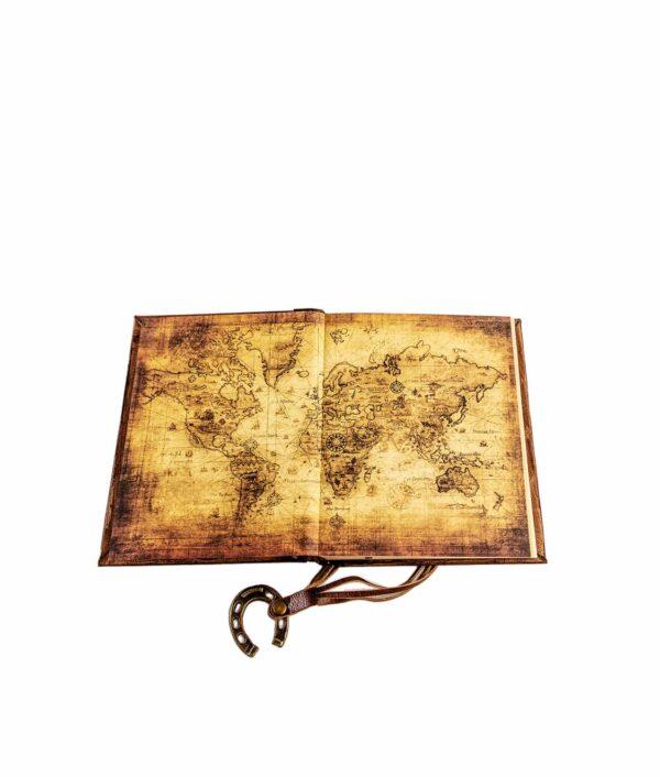 Lederbuch geöffnet mit Hufeisen und Weltkarte.